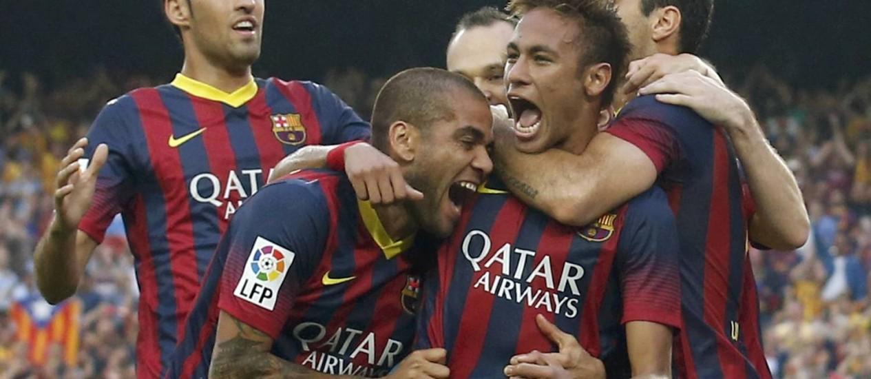 Neymar é abraçado por Daniel Alves e Sergio Busquets após marcar um gol no Camp Nou, em seu primeiro Barcelona x Real Madrid Foto: ALBERT GEA / REUTERS