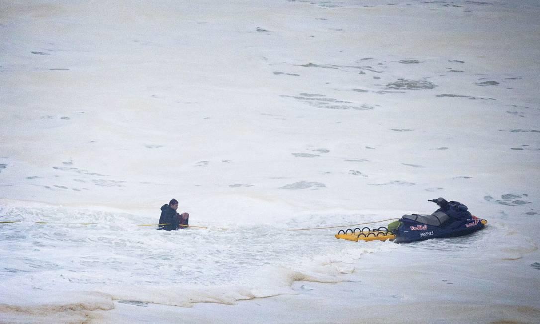 O surfista brasileiro Carlos Burle ajuda no resgate da colega Maya Gabeira Miguel Barreira / AP