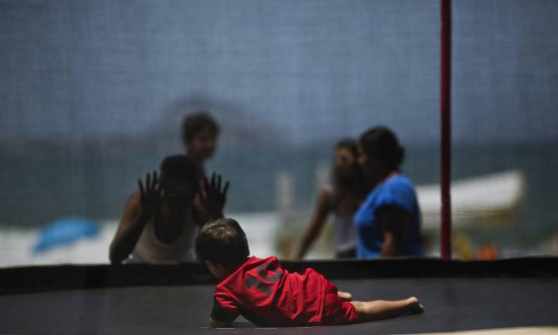 De frente para a orla, com uma rede mais segura, criança pequena brinca sozinha em uma cama elástica Foto: Fábio Seixo / Agência O Globo