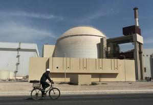 Trabalhador passa de bicicleta em frente a um reator na usina nuclear de Bushehr Foto: Majid Asgaripour / AP