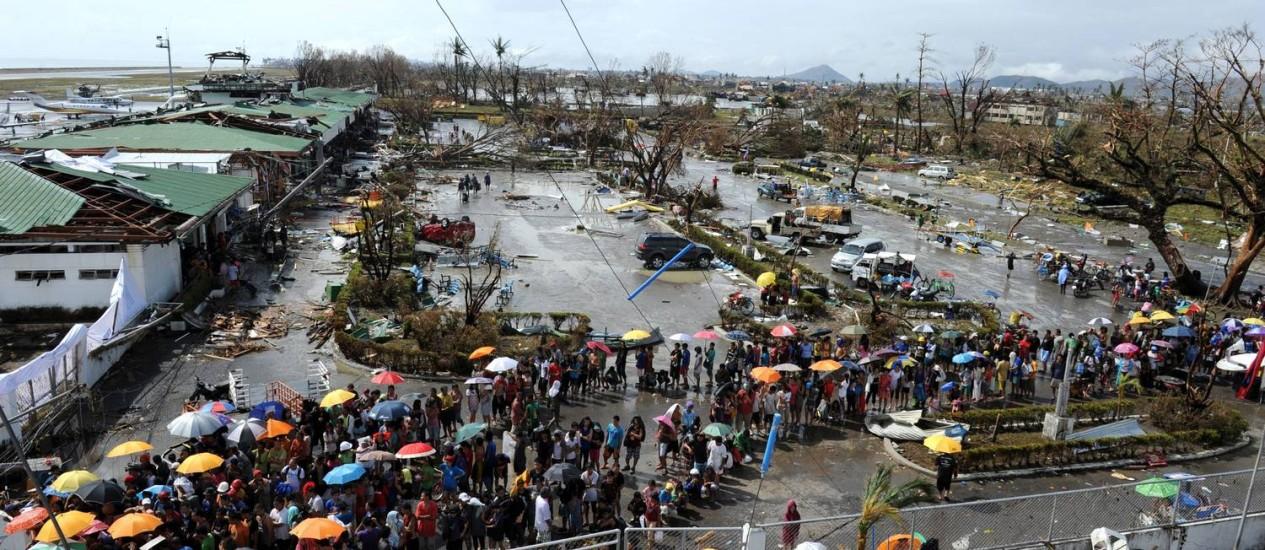 Sobreviventes da passagem do tufão Haiyan fazem fila entre escombros do aeroporto de Tacloban para receber ajuda humanitária Foto: TED ALJIBE / AFP