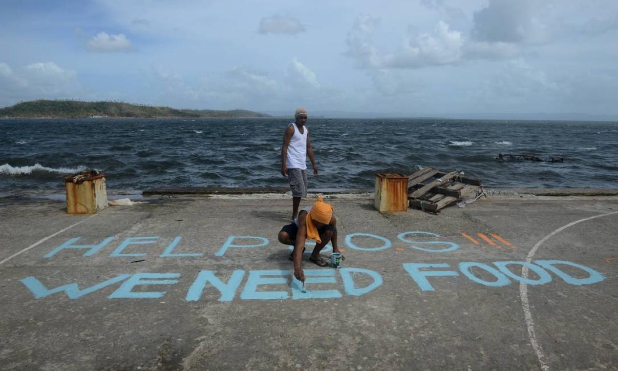 """Os moradores usaram uma quadra de basquete para pedir ajuda. A mensagem, em inglês, diz: """"Socorro, precisamos de comida!"""" Foto: NOEL CELIS / AFP"""