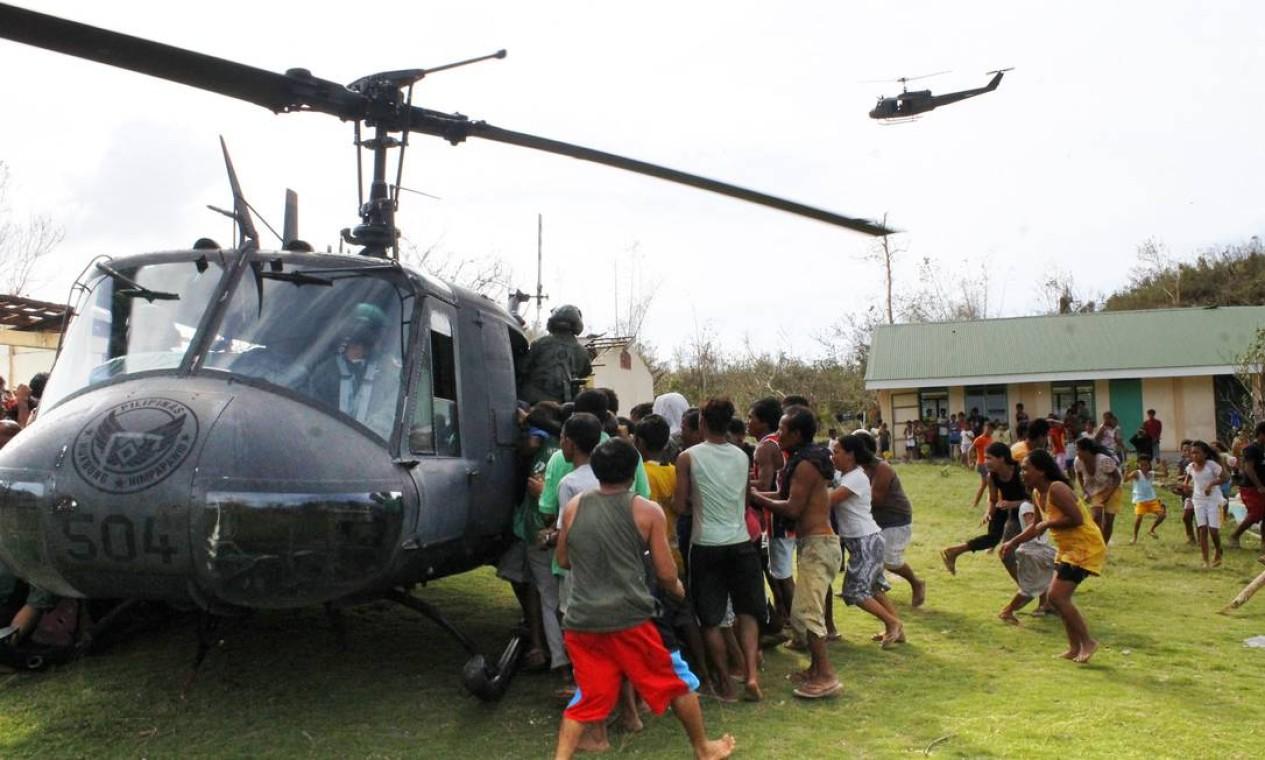 Após a chegada de um helicóptero militar, moradores da província Iloilo correram para garantir mantimentos durante o trabalho de rescaldo feito para ajudar os sobreviventes Foto: STRINGER/PHILIPPINES / Reuters