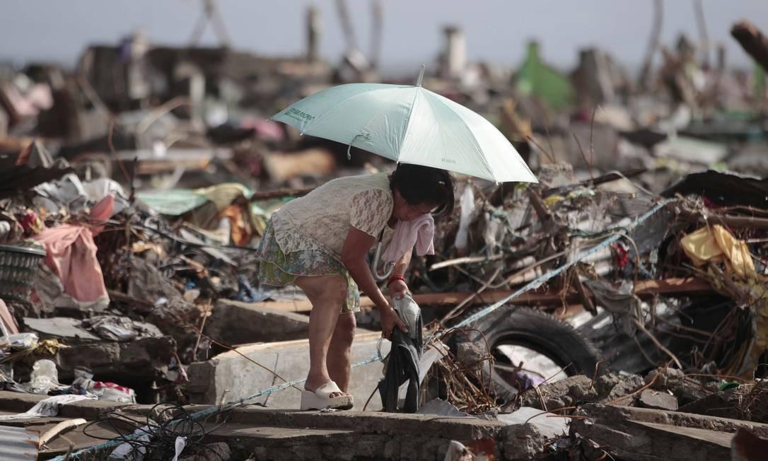 Uma sobrevivente tenta salvar os pertences de sua casa, que foi completamente destruida pelo tufão, em Tacloban. Segundos as autoridades, 41 províncias foram afetadas e pelo menos 23 mil casas foram danificadas ou destruídas Foto: Aaron Favila / AP
