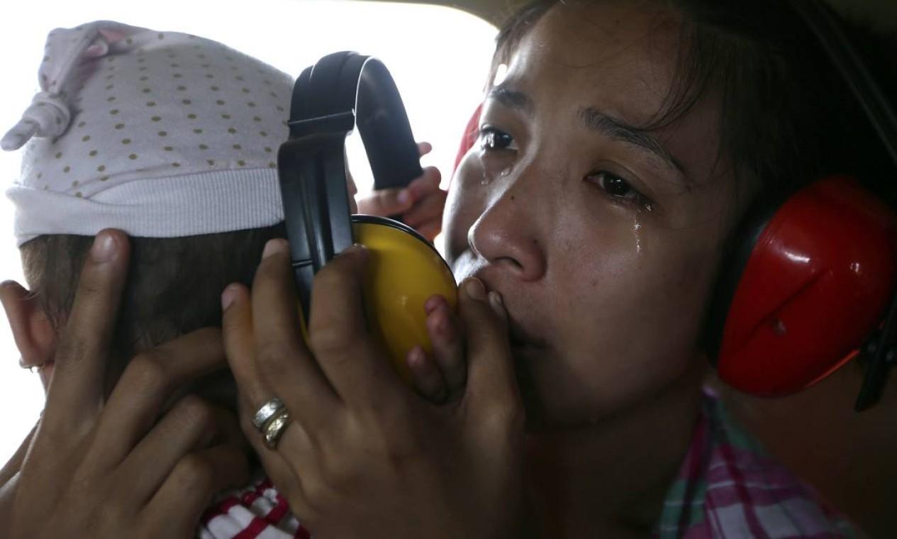 Uma mãe chora de alívio, após conseguir embarcar com o filho em um helicóptero das Forças Armadas, para deixar a cidade de Guiuan, nesta segunda-feira Foto: Bullit Marquez / AP