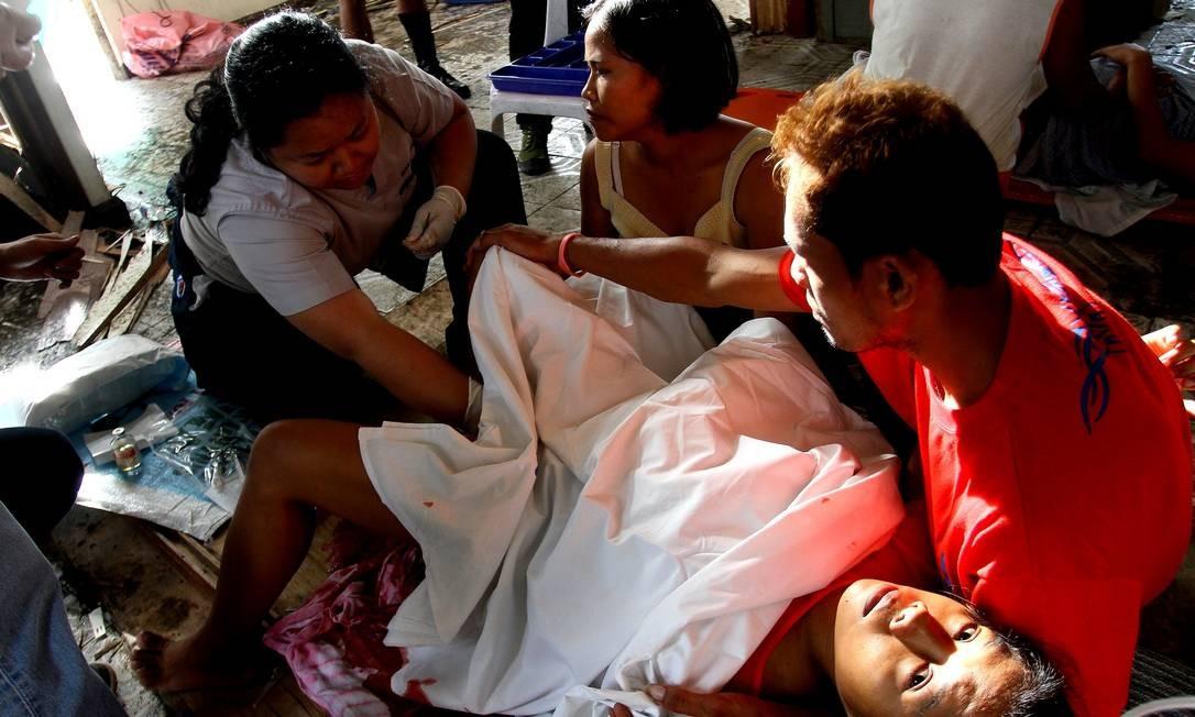 """Em um aeroporto destruído de Tacloban, que virou um acampamento médico improvisado, uma equipe ajuda Emily Sagalis a dar à luz. Nascimento do bebê foi considerado um """"milagre"""" Foto: JASON GUTIERREZ / AFP"""