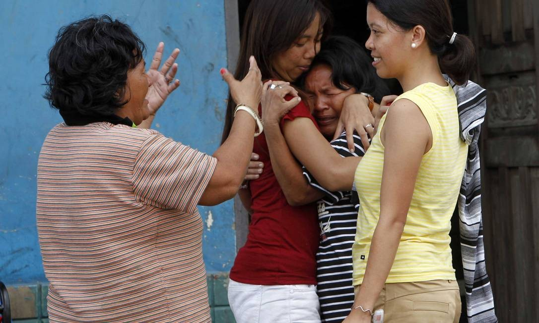 Ao se reencontrarem pela primeira vez após a passagem do supertufão, moradoras de Tacloban se abraçam e choram emocionadas Foto: ROMEO RANOCO / REUTERS