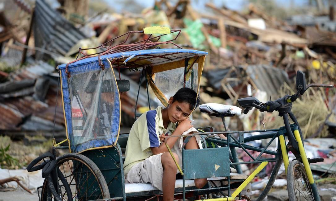 Um jovem sobrevivente descansa desolado em um triciclo, rodeado por destroços Foto: NOEL CELIS / AFP