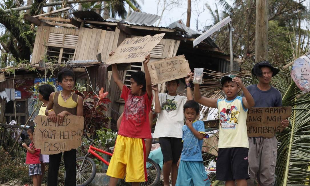 Crianças e jovens filipinos seguram cartazes com pedidos de ajuda, a maioria escritos em inglês, depois da destruição provocada pelo tufão que deixou milhares de mortos no país Foto: CHARLIE SACEDA / Reuters
