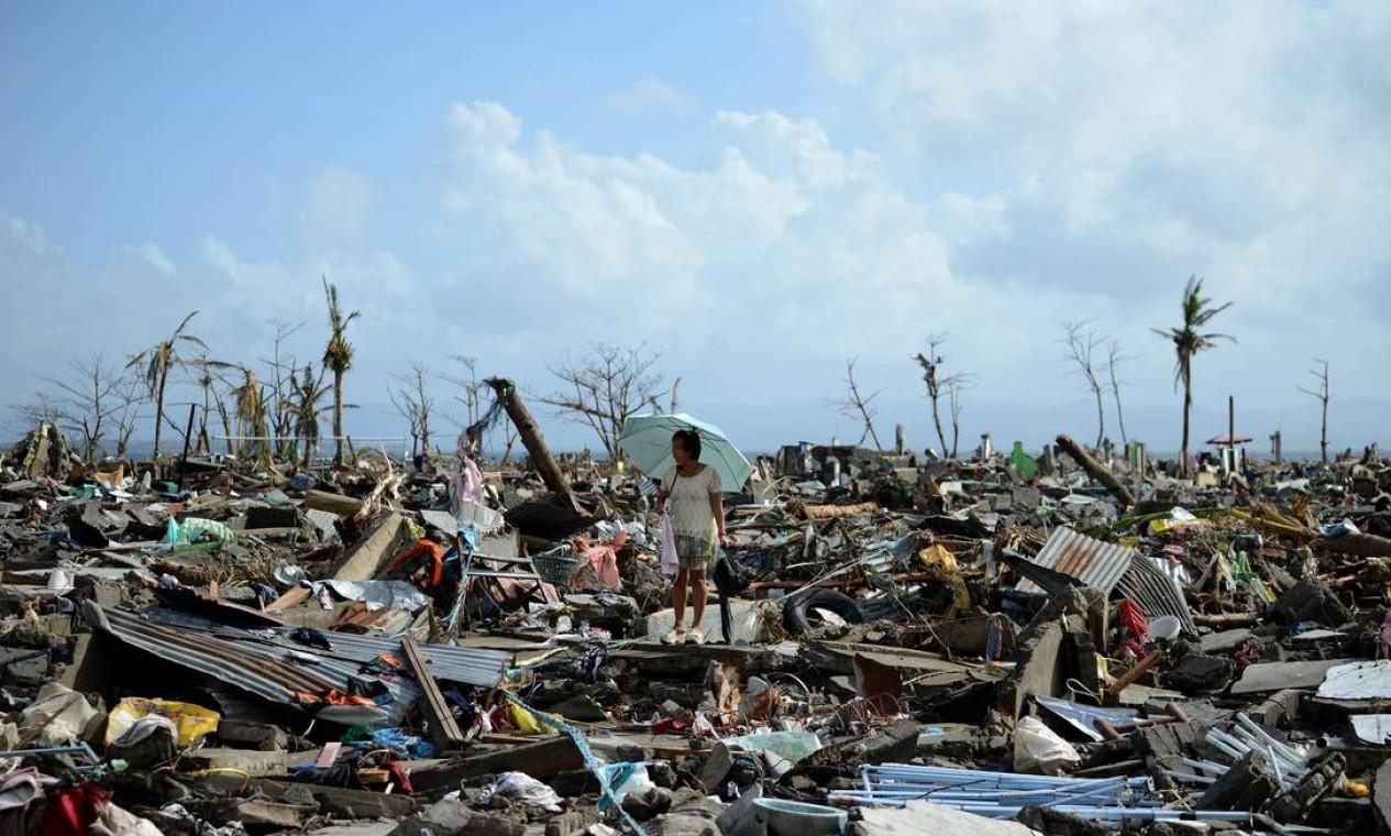 Sobrevivente caminha sobre destroços provocados pelo tufão que matou milhares nas Filipinas Foto: NOEL CELIS / AFP