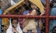 Sobreviventes do Tufão aguardam atrás de uma cerca no aeroporto Tacloban por um espaço na aeronave que os levará à capital Manila
