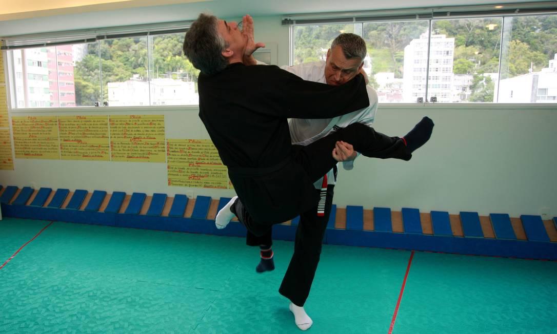 Reylson Gracie demonstra, em um aluno, um golpe de jiu-jítsu Foto: Pedro Teixeira