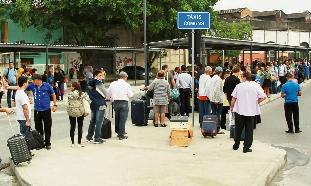 Passageiros da Rodoviária Novo Rio enfrentam uma fila quilométrica para pegar um táxi, ao lado do terminal, após a volta do feriado prolongado: a espera se estendeu por mais de uma hora, reclamavam eles Foto: Gabriel de Paiva