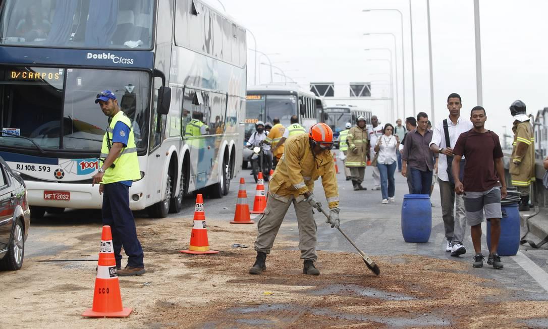 Homem limpa a pista na descida da Ponte Rio-Niterói, onde três ônibus e um carro colidiram na manhã desta sexta-feira Márcia Foletto / Agência O Globo