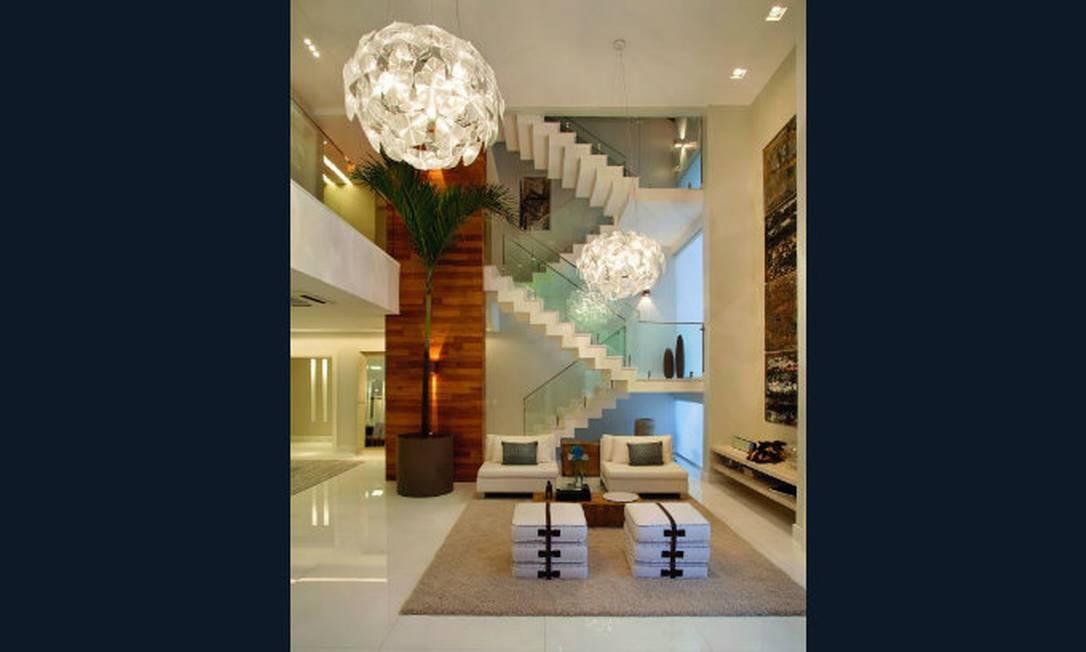 Duas grandes luminárias e um enorme palmeira para preencher a sala desta casa na Barra da Tijuca. Projeto de Claudia Pimenta e Patricia Franco Foto: Divulgação