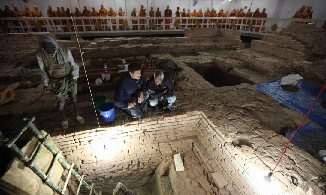 Arqueólogos Robin Coningham e Kosh Prasad Acharya nas escavações do templo Maya Devi; ao fundo monges tailandeses meditam. Foto: National Geographic / Ira Block