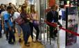 Venezuelanos fazem fila para entrar numa loja de departamentos em shopping de Caracas
