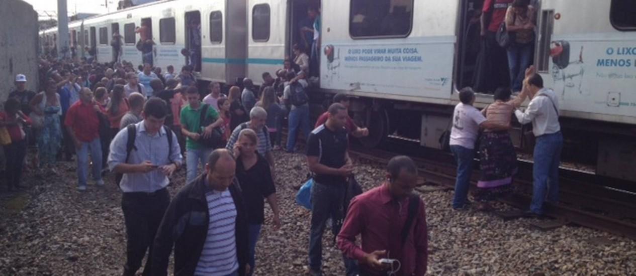 Passageiros caminham ao lado de trem que descarrilou perto da estação do Engenho de Dentro Foto: Rennan Setti / O Globo