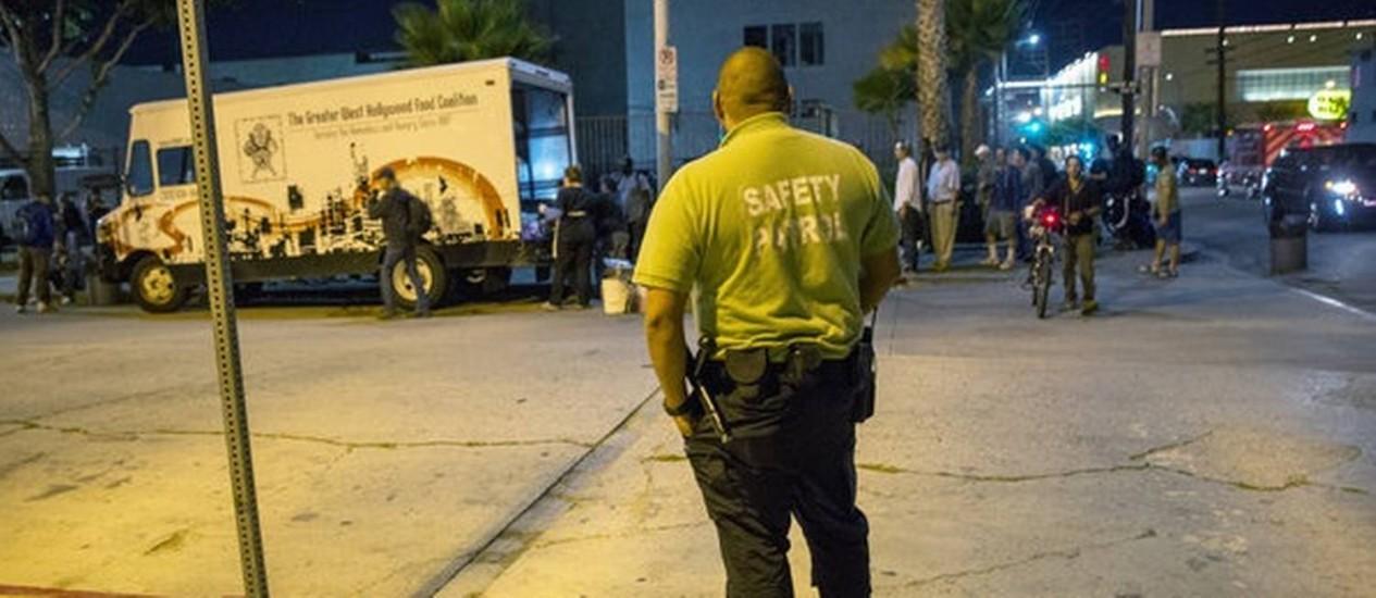 Segurança observa caminhão do Greater West Hollywood Food Coalition que chega com refeições para a população carente em Los Angeles Foto: Monica Almeida/The New York Times