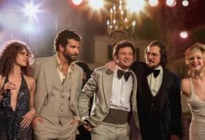 Bradley Cooper (à esqueda) e Jennifer Lawrence (na extrema direita) atuam de novo juntos, depois de 'O lado bom da vida', em 'Trapaça' Foto: Divulgação