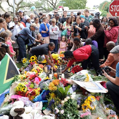 Sul-africanos deixam flores e ascendem velas em frente à casa de Nelson Mandela, em Joanesburgo Foto: STEPHANE DE SAKUTIN / AFP