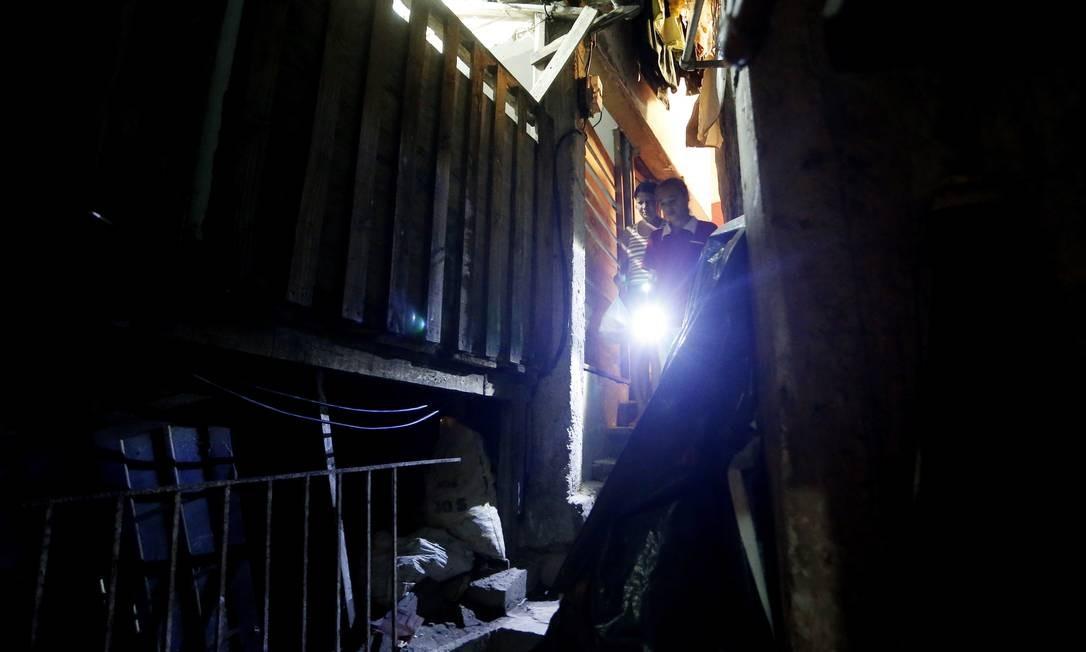 Moradores do Dona Marta usam lanterna em viela da favela Foto: Guito Moreto / O Globo