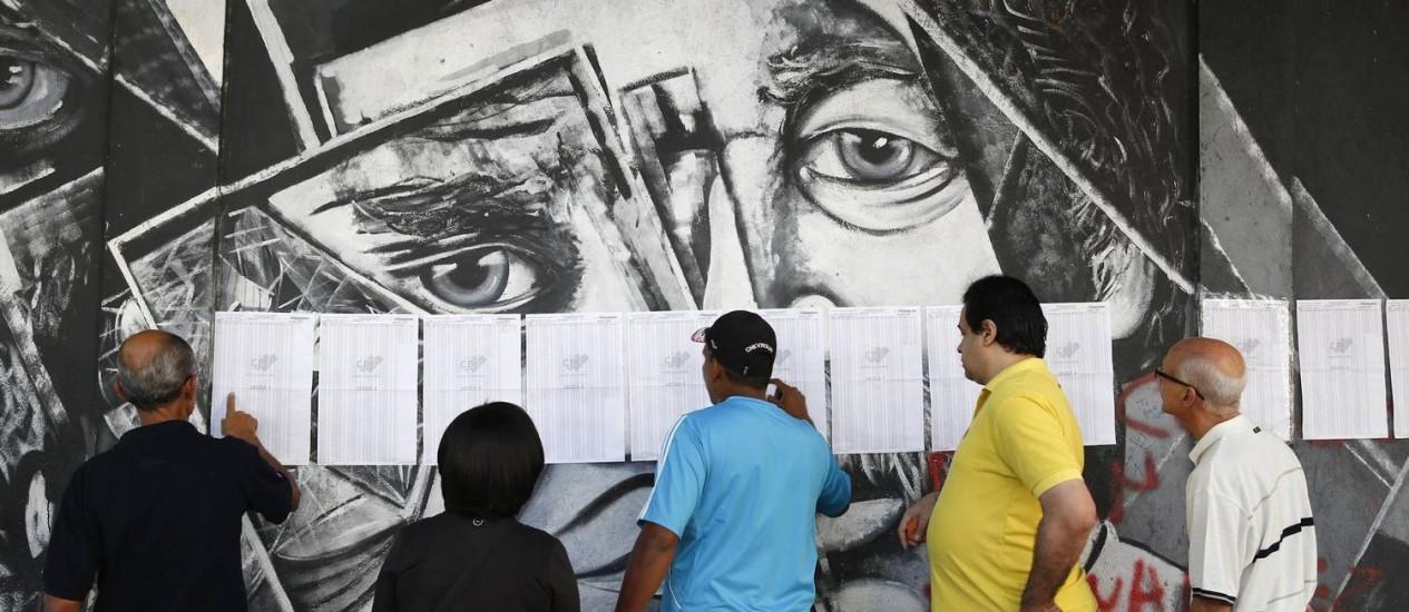 Venezuelanos buscam números de identificação em listas numa sessão eleitoral de Caracas Foto: Carlos Garcia Rawlins / REUTERS