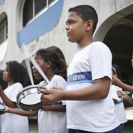 Alunos de um Ciep no Morro do Borel aprendem a tocar tamborim no pátio: antes da UPP, atividades ao ar livre eram um perigo, por causa dos constantes tiroteios - Foto: Guito Moreto / Agência O Globo