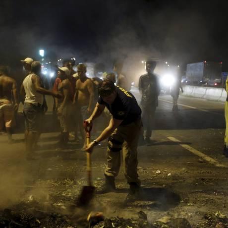 Agente da Polícia Rodoviária Federal ajuda a tirar o material queimado no meio da pista sentido Itaboraí Foto: Felipe Hanower / Agência O Globo