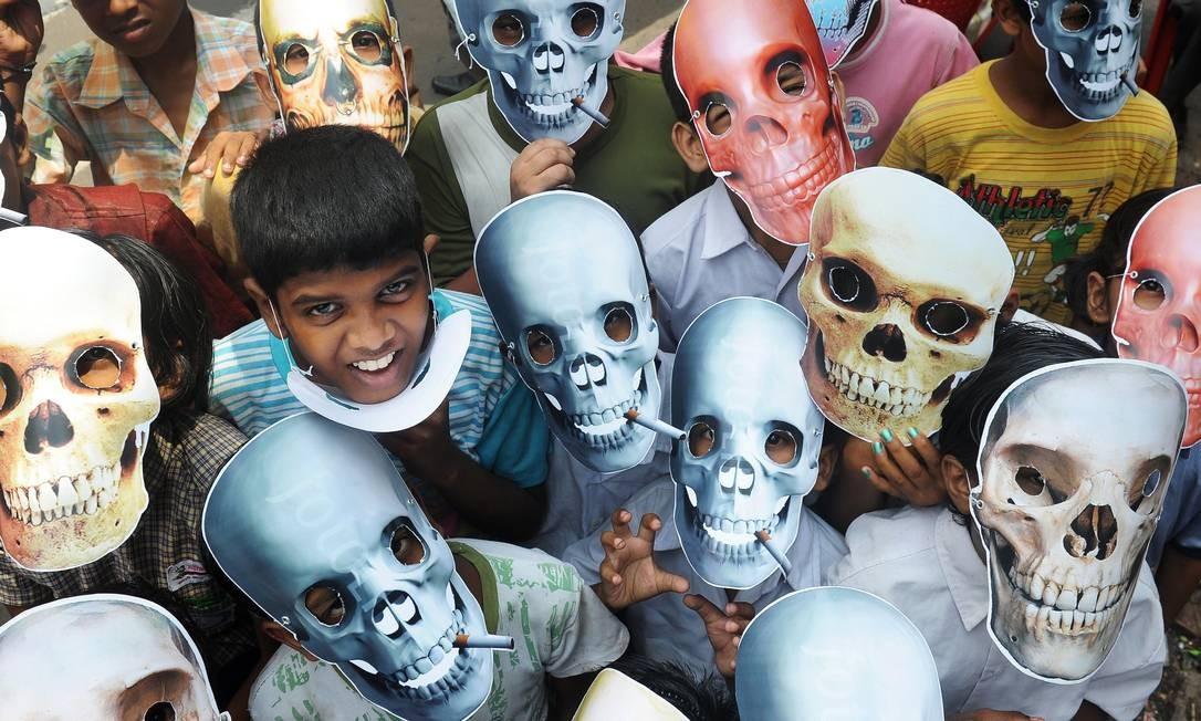 Dia mundial sem tabaco. Crianças usam máscaras de caveiras na Índia, em evento para marcar a data e frisar a importância da prevenção para a redução de mortes Foto: DIBYANGSHU SARKAR / Dibyangshu SARKAR/AFP