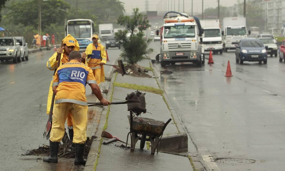 Funcionários da prefeitura limpam bueiros na Avenida Brasil, em Irajá Foto: Gabriel de Paiva / Agência O Globo
