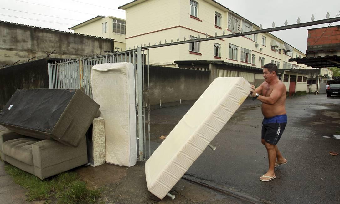 Jorge Luiz Costa empilha os móveis perdidos no temporal Foto: Gabriel de Paiva / Agência O Globo