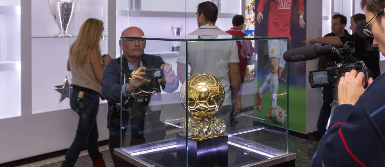 Pessoas tiram foto e filmam um troféu em formato de bola de futebol no Museu dedicado ao craque português Cristiano Ronaldo Foto: GREGORIO CUNHA / AFP