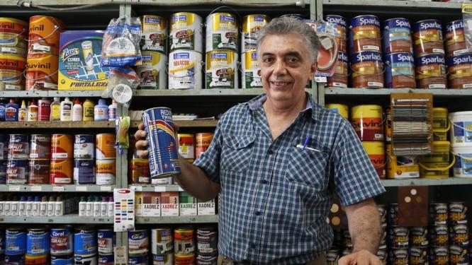 Em sua loja de materiais de construção, o comerciante Herbert Parente mostra lata de thinner, produto usado na remoção da pichação na estátua de Carlos Drummond de Andrade, que já foi cliente do estabelecimento, ainda no antigo endereço em Copacabana Foto: Simone Marinho / O Globo