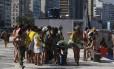 Turistas fazem fila para fazer foto ao lado da estátua de Carlos Drummond de Andrade, em Copacabana