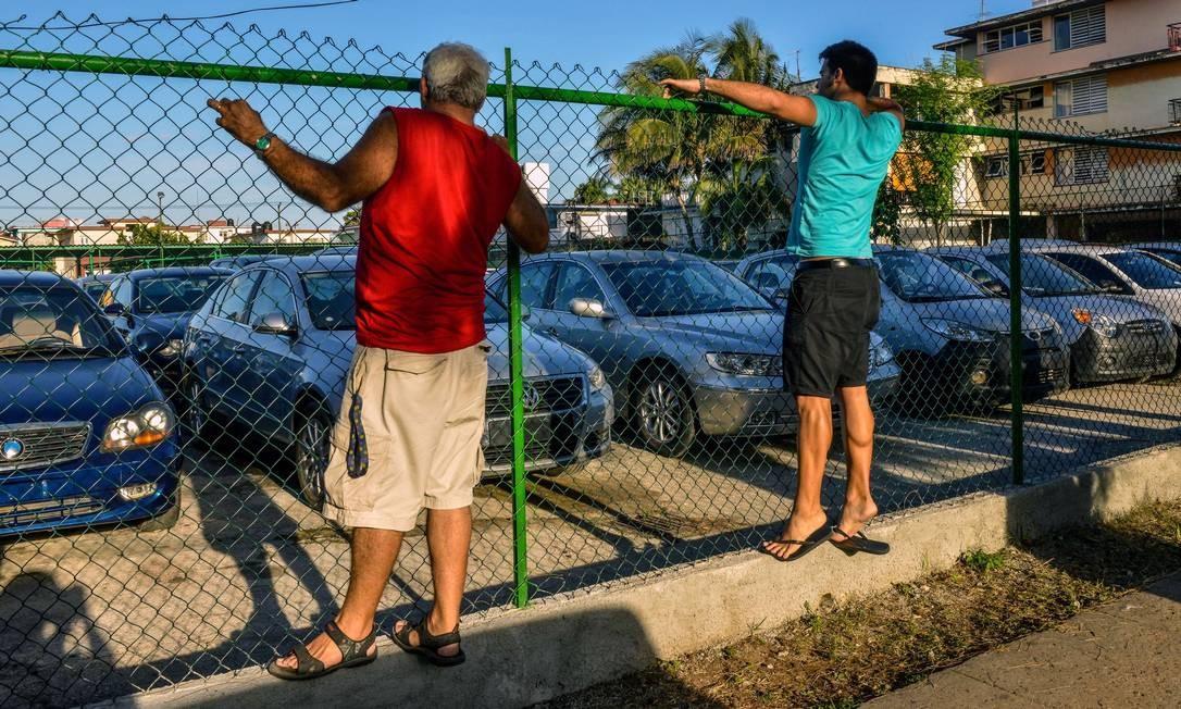 Cubanos observam carros usados à venda em Havana: nova regulamentação divulgada pelo presidente Raul Castro permitirá que cubanos e estrangeiros residentes comprem carros novos ou usados em lojas determinadas pelo governo Foto: ADALBERTO ROQUE / AFP