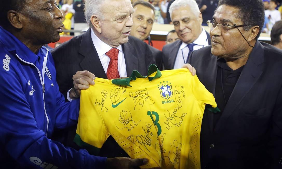 Nesta foto de setembro de 2013, Pelé e Eusébio seguram uma camisa da seleção brasileira autografada, junto ao presidente da Confederação Brasileira de Futebol, José Maria Marin (centro), antes do amistoso entre Brasil e Portugal, no Foxborough, Massachusetts. Foto: BRIAN SNYDER / REUTERS