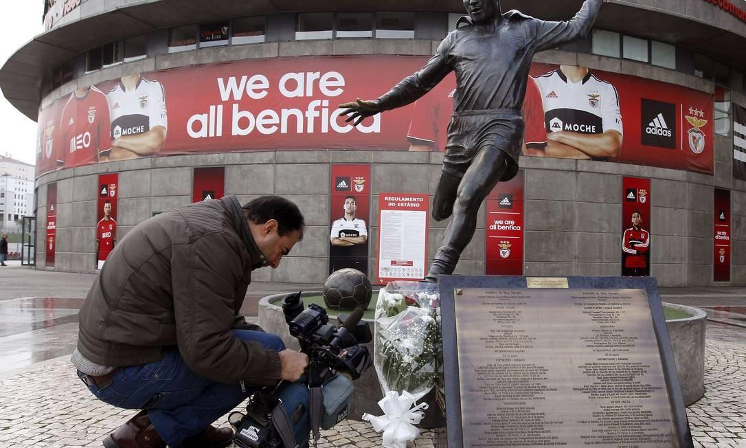 Um cameraman filma a estátua de Eusébio, que amanheceu com flores, após o anúncio da morte do ex-atacante Foto: JOSE MANUEL RIBEIRO / AFP