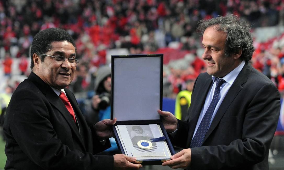 Eusébio recebe uma placa comemorativa das mãos do francês Michel Platini, presidente da UEFA, no Estádio da Luz, em Lisboa. Eusébio foi eleito o jogador do ano em 1965 e eleito craque da Copa de 1966, na Inglaterra Foto: FRANCISCO LEONG / AFP