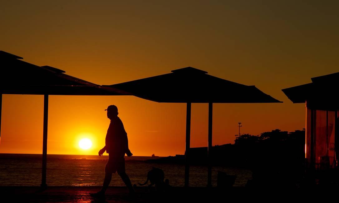 Homem caminha no calçadão da Praia de Copacabana ao amanhecer Foto: Fernando Quevedo / Agência O Globo
