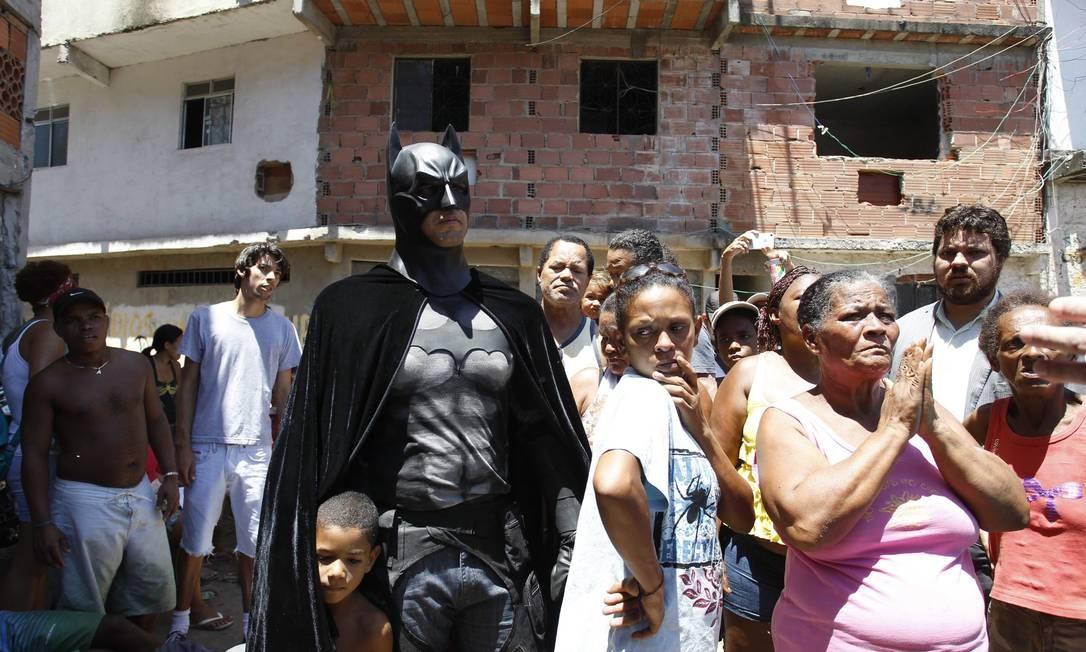 Criança se esconde sob a capa de homem fantasiado de Batman na Favela Metrô-Mangueira Foto: Pablo Jacob / Agência O Globo