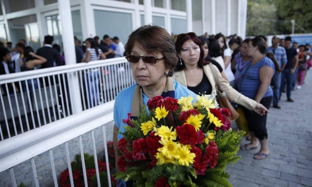 Mulher leva flores para enterro de ex-miss Mónica Spear Foto: Carlos Garcia Rawlins / REUTERS