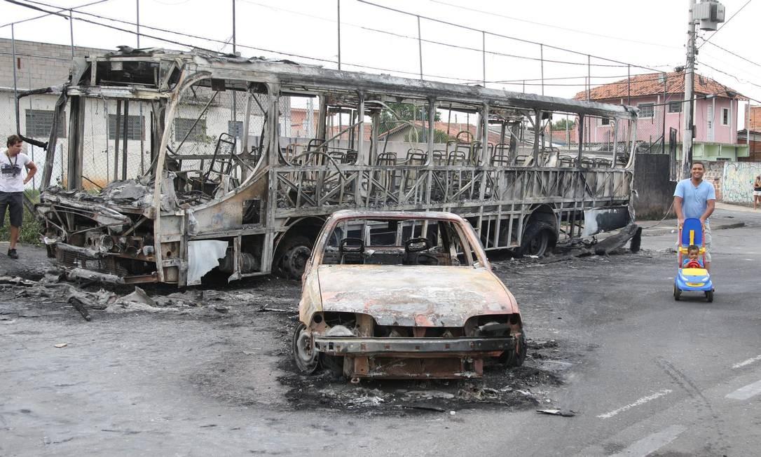 Homem passeia com criança ao lado de carro e ônibus queimados em Campinas (SP) Foto: Marcos Alves / O Globo