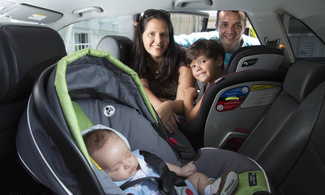 Casal precavido usa a cadeirinha para proteger dois filhosFoto: Leo Martins / O Globo