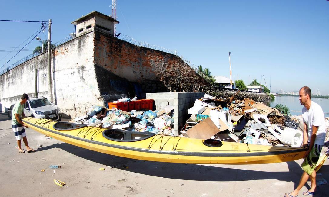 Cercados por lixo jogado na borda da Baía de Guanabara no Caju, Bruno Fitaroni e Rafael Cajá carregam um caiaque oceânico para o mar: no trecho, o mau cheiro e a água cinza, tomada por esgoto, predominam Foto: Marcelo Piu / Agência O Globo