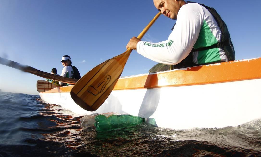 Os adeptos da canoa havaiana também têm a poluição como obstáculo à atividade. Na foto, um remador tenta afastar garrafas pet da rota das embarcações Foto: Marcelo Piu / Agência O Globo