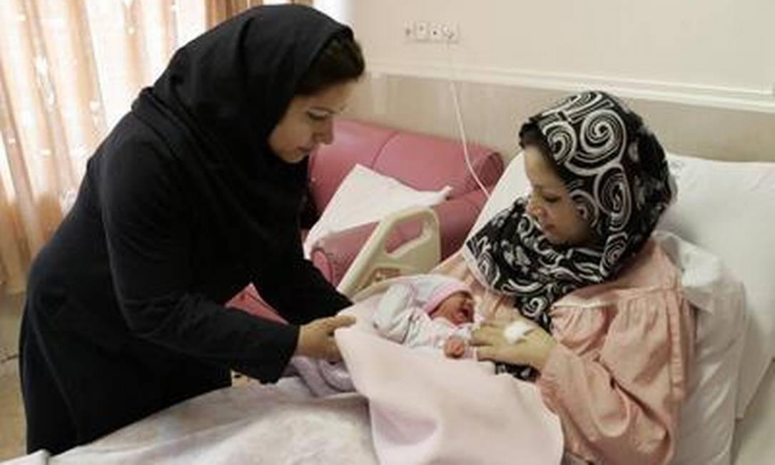 A iraniana Tayyebeh Sadat Bidaki recebe seu bebê de uma enfermeira em Teerã Foto: AP-30-7-2012