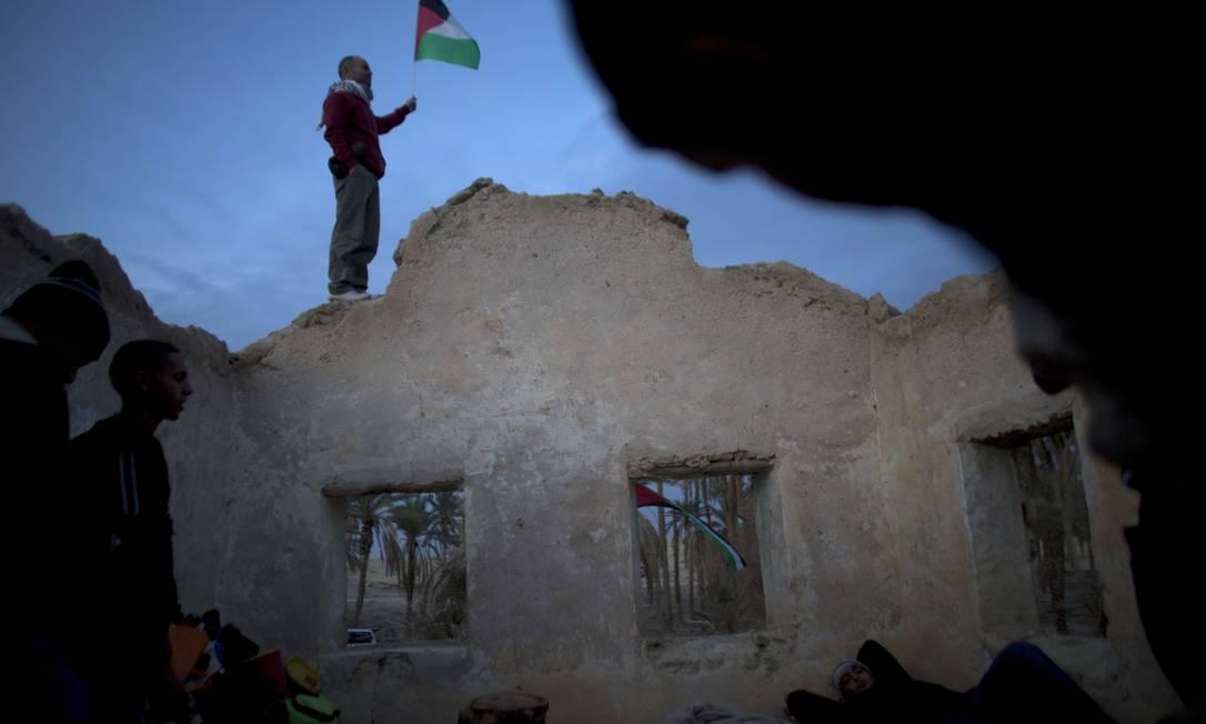Ativista segura bandeira palestina em uma casa abandonada perto de Jericó, na Cisjordânia ocupada Foto: AHMAD GHARABLI / AFP