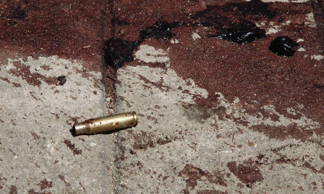 Cápsula deflagrada no chão de rua da comunidade Foto: Marcos Tristão / O Globo