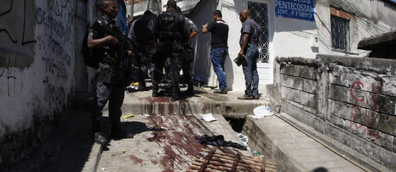 Policiais militares durante operação no Morro do Juramento. No chão, marcas de sangue Foto: Marcos Tristão / O Globo